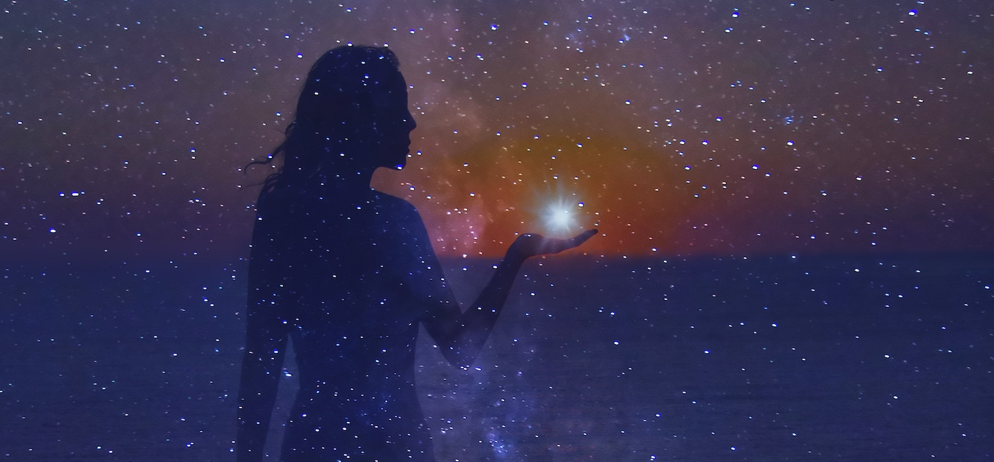 Woman holding a shining star in her hand in the colorful dreamy night sky