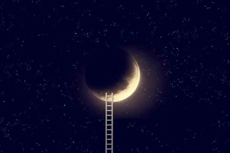 Ladder leading up to crescent moon in night sky