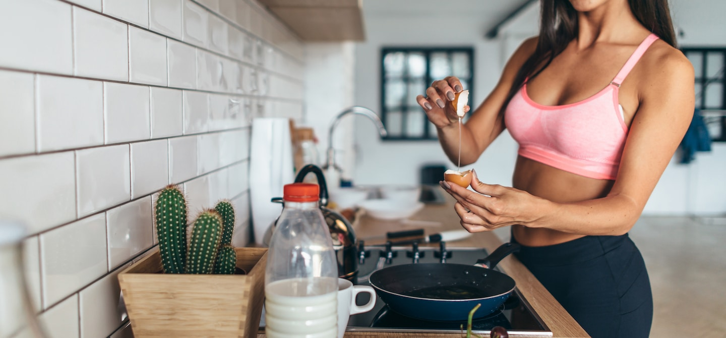 Woman cracking eggs making a healthy breakfast