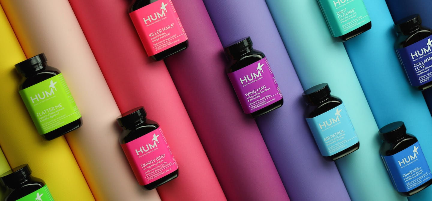 HUM Nutrition supplement bottles on rainbow spectrum
