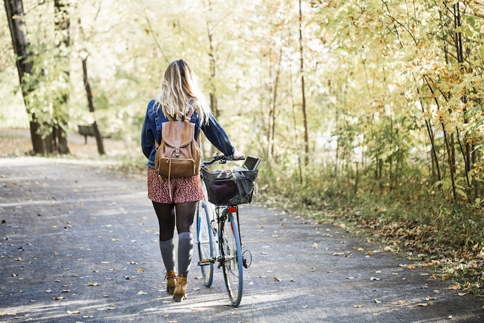 Healthy lifestyle woman walking with bike in fall