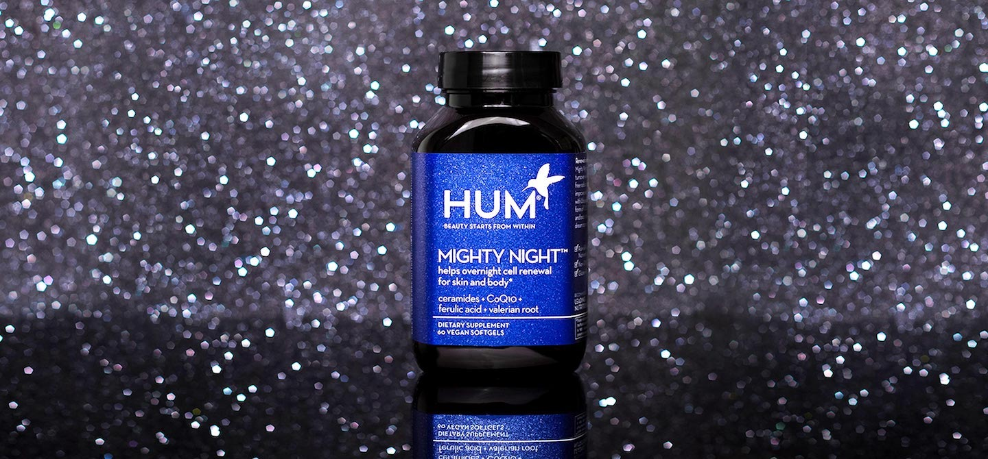 Bottle of HUM Nutrition Mighty Night supplement for skin cell renewal amidst dark starry background