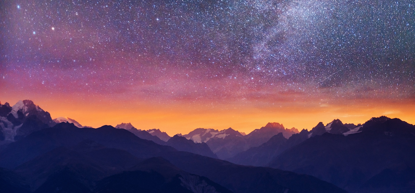 Purple pink and orange starry night sky in the mountains