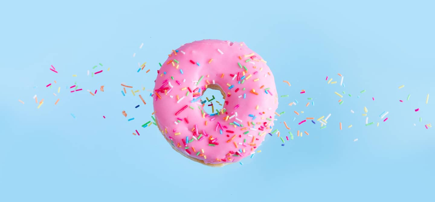 Pink donut floating over blue background