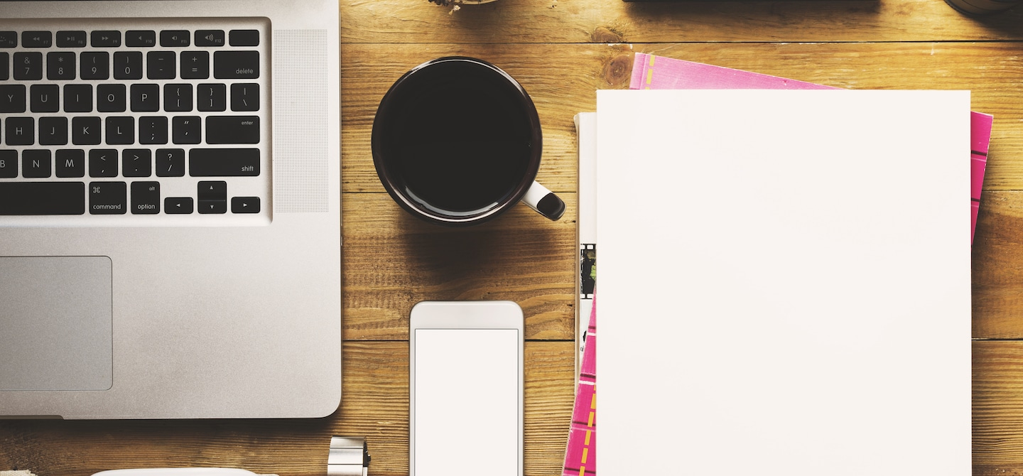 Desk with laptop, coffee, phone, and notebooks organized for optimal productivity