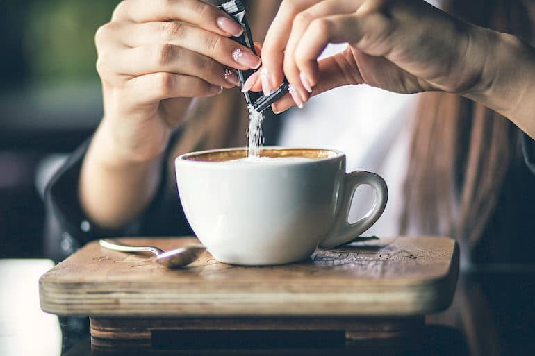 Woman adding sugar to her coffee