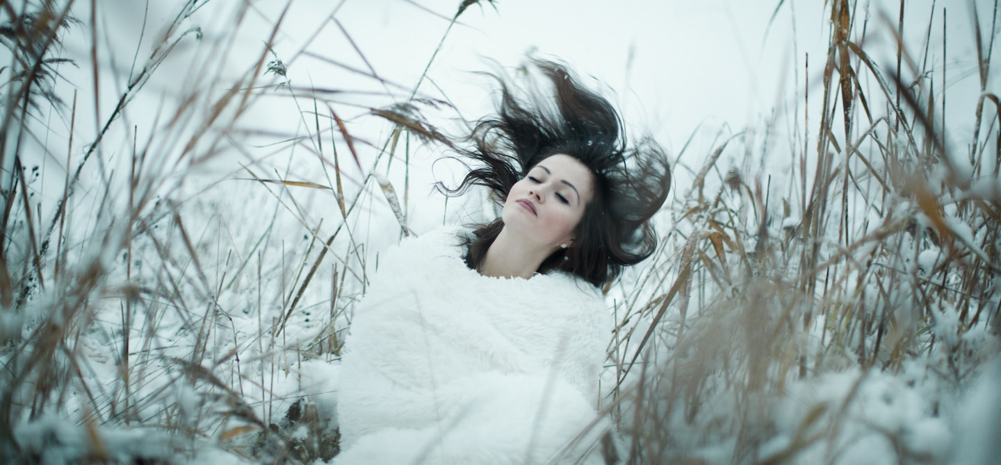 Woman flipping her dark hair in a field in winter