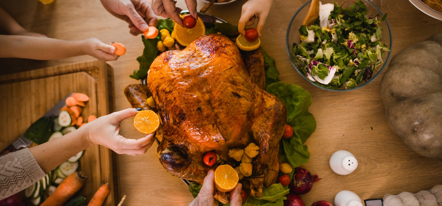 High angle shot of family members decorating Thanksgiving turkey with citrus