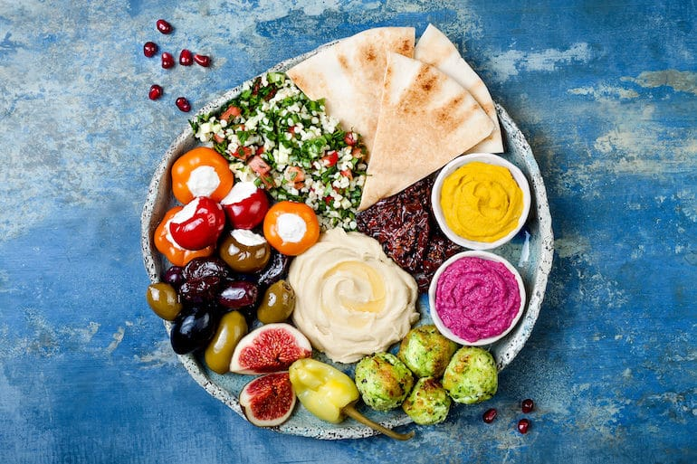 Mediterranean Diet Middle Eastern meze platter with green falafel, pita, sun dried tomatoes, pumpkin and beet hummus, olives, stuffed peppers, tabbouleh, figs. Mediterranean appetizer party idea (Middle Eastern meze platter with green falafel, pita, sun dried tomatoes