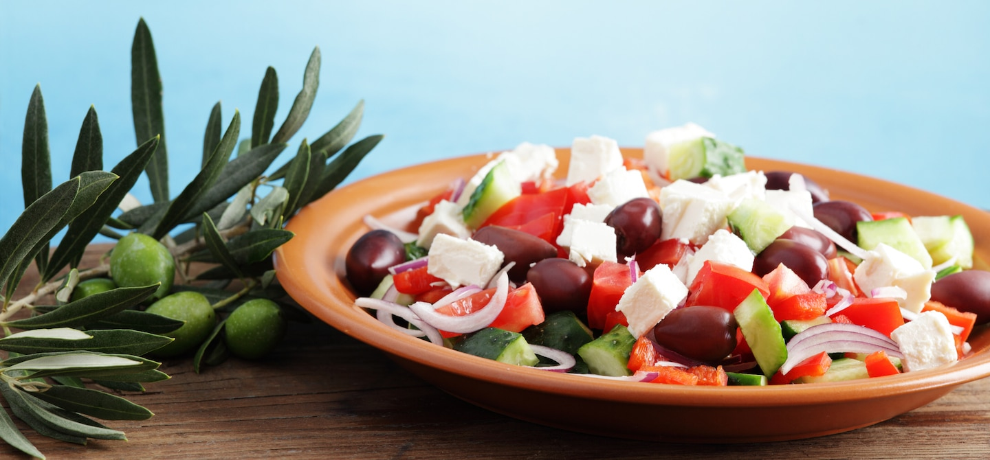 Greek salad on table with Mediterranean Sea in background