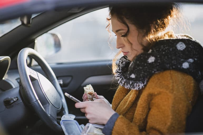 Woman with bad habit of eating in the car while looking at her phone