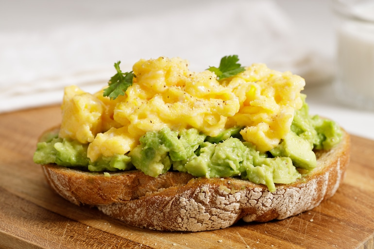 Scrambled eggs on avocado toast for hungover breakfast