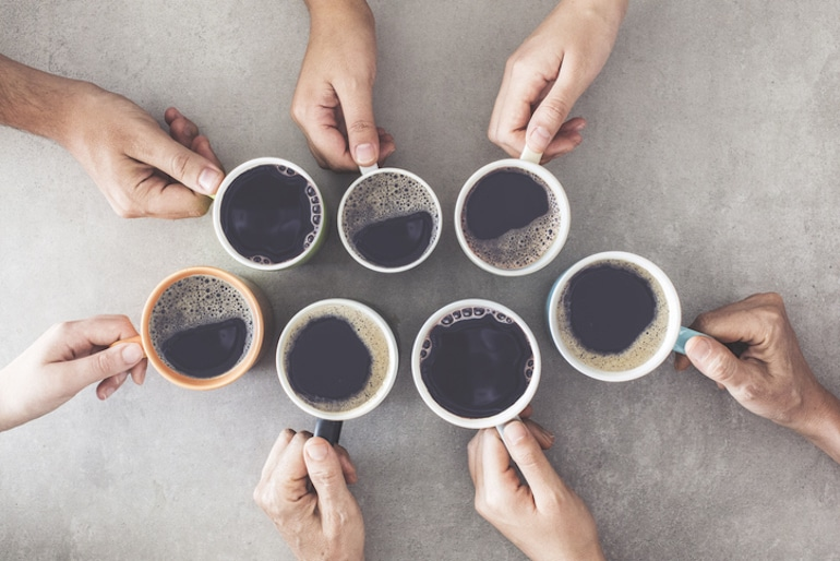 Overhead group shot of people's hands holding coffee mugs