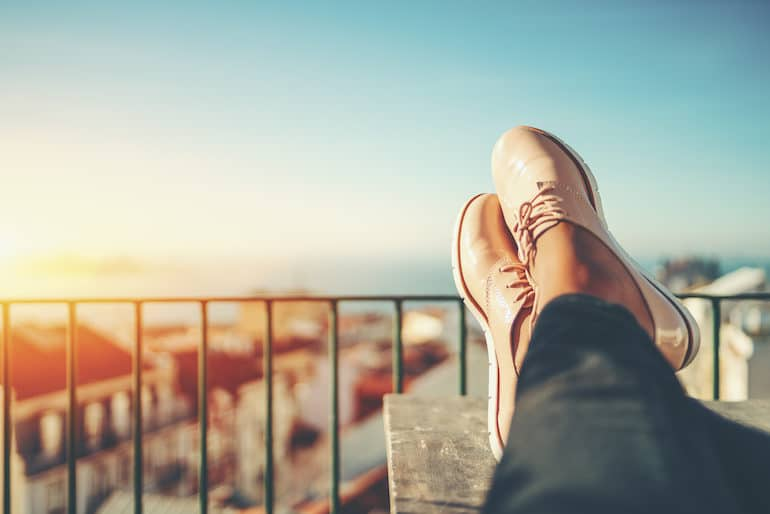 Woman with feet up on balcony enjoying the present moment on a social media detox