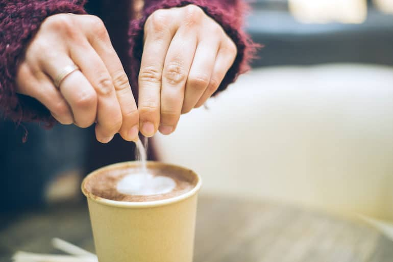 Woman pouring aspartame in coffee