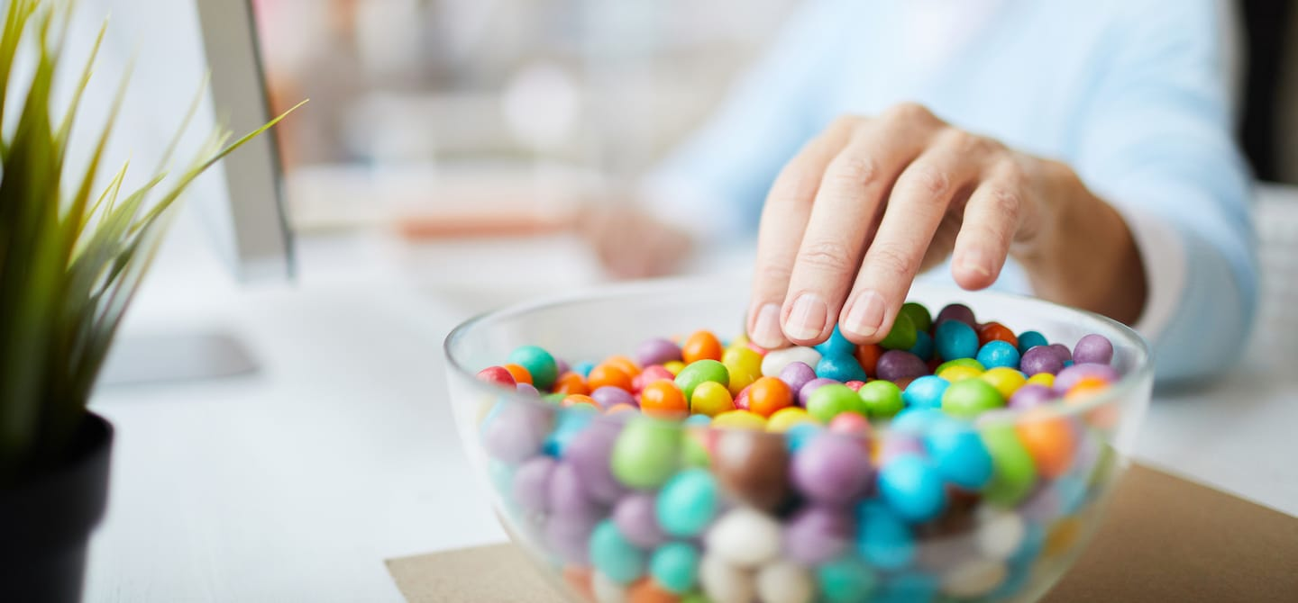 Woman's hand reaching for candy while working