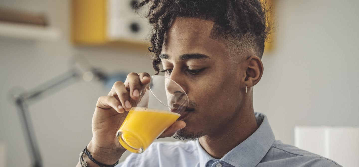 Young man sipping orange juice, which is high in vitamin D