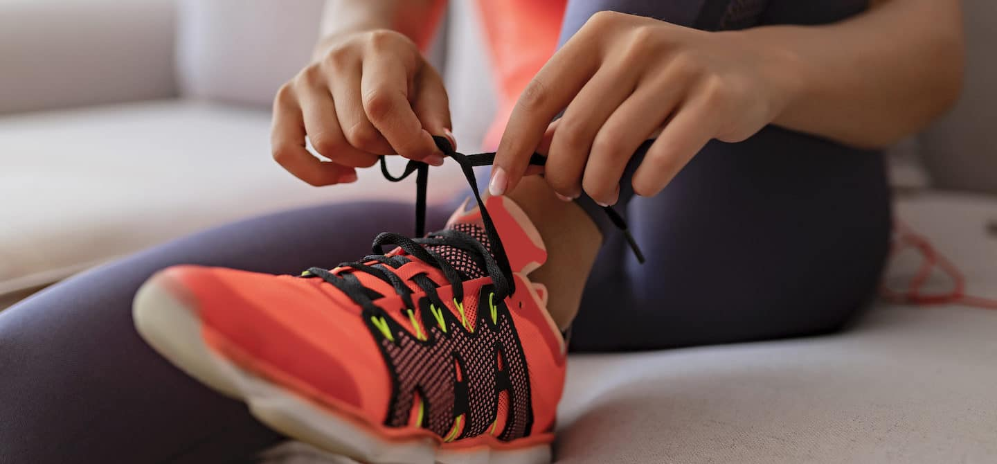 Woman tying running shoes for 2020 resolution to run more.