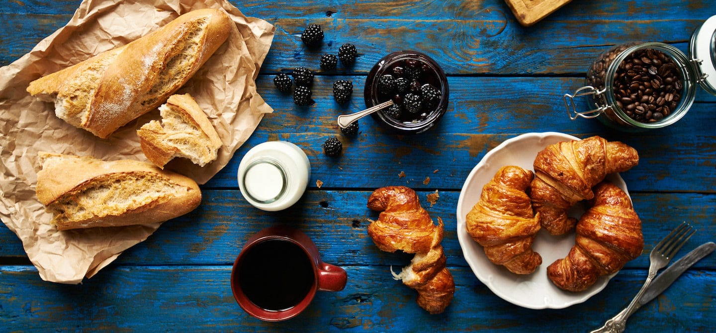 Bread, coffee, croissants, and other foods to avoid for clear skin on a blue wooden table