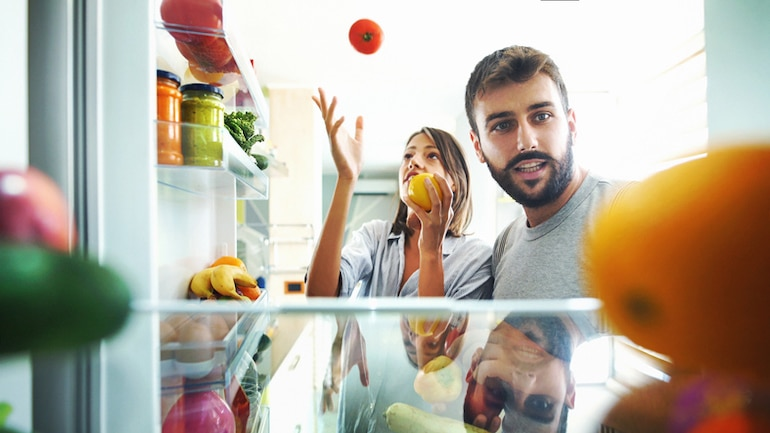 Young couple detoxing their kitchen in front of fridge with fruits and vegetables