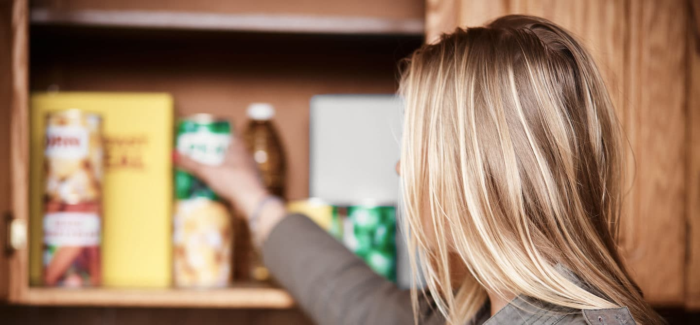 Blonde woman reaching in her pantry to detox her kitchen