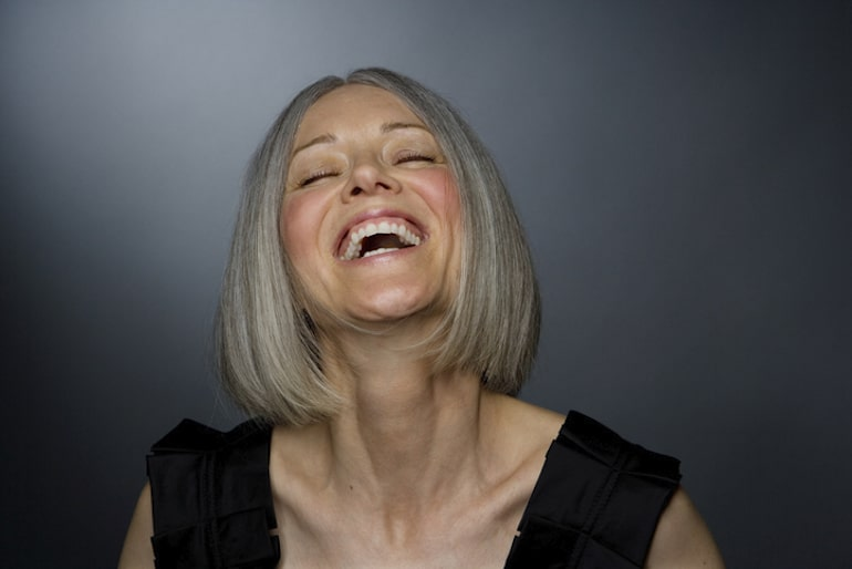 Mature woman laughing, with no wrinkles because she takes different types of collagen for plump skin