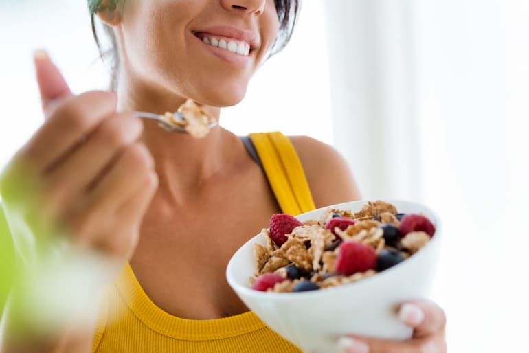 Young woman eating fortified cereal, a good source of vitamin D, with berries