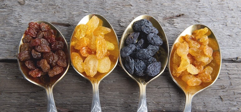 Four spoonfuls of dried fruit on wooden table