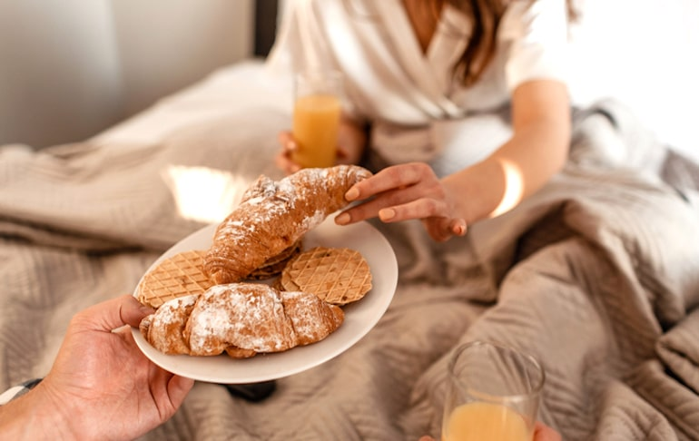 Couple eating croissants in bed to demonstrate link between gluten anc acne