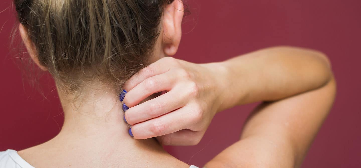 Back of woman scratching her neck