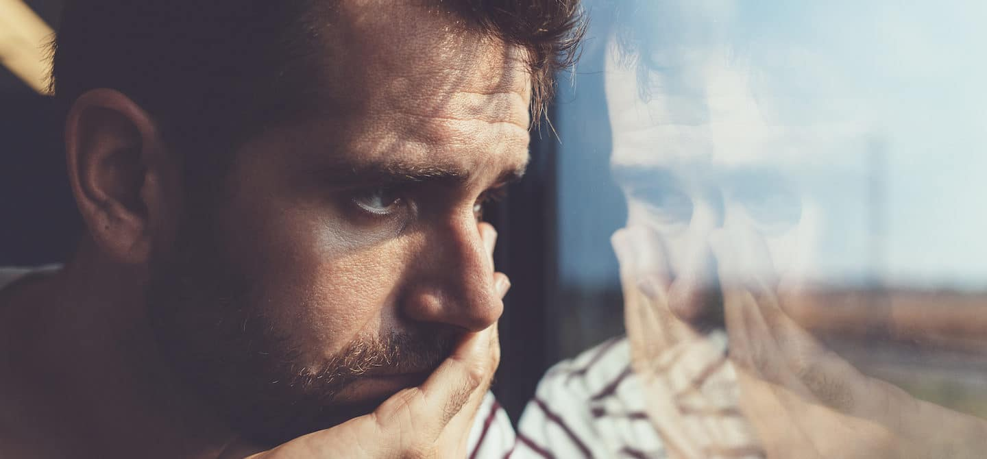 Sad young man looking through the window, discouraged by his own negative self-talk