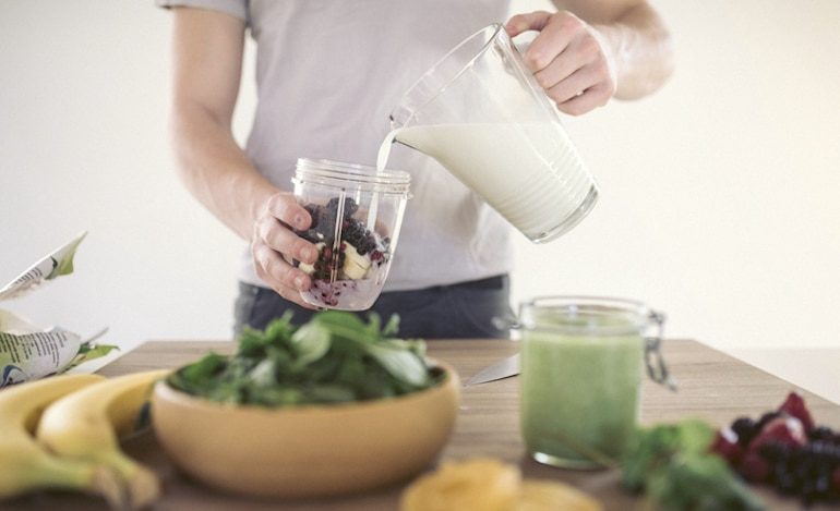 Man pouring milk into a smoothie