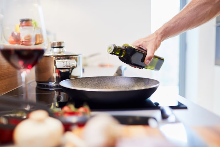 Man pouring unhealthy oil into pan on stove