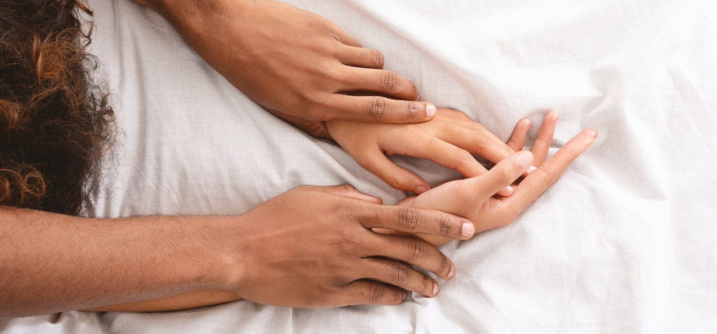 Hands on man and woman in bed, likely using sex toys