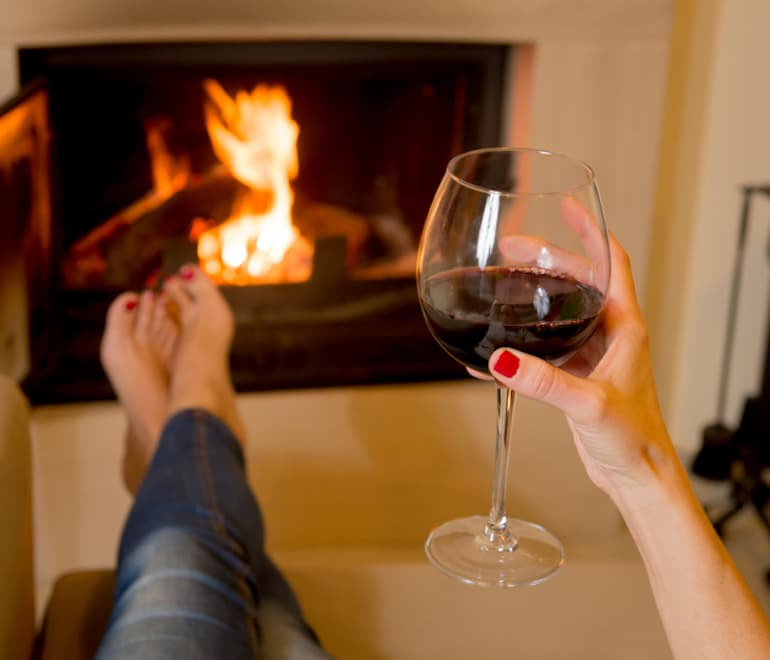 Woman holding a glass of red wine with legs kicked up at the fireplace for an anxiety-free Valentine's Day