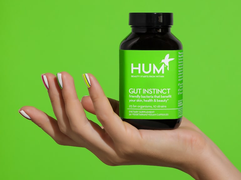 Woman's hand holding HUM Gut Instinct probiotic supplement in front of green background
