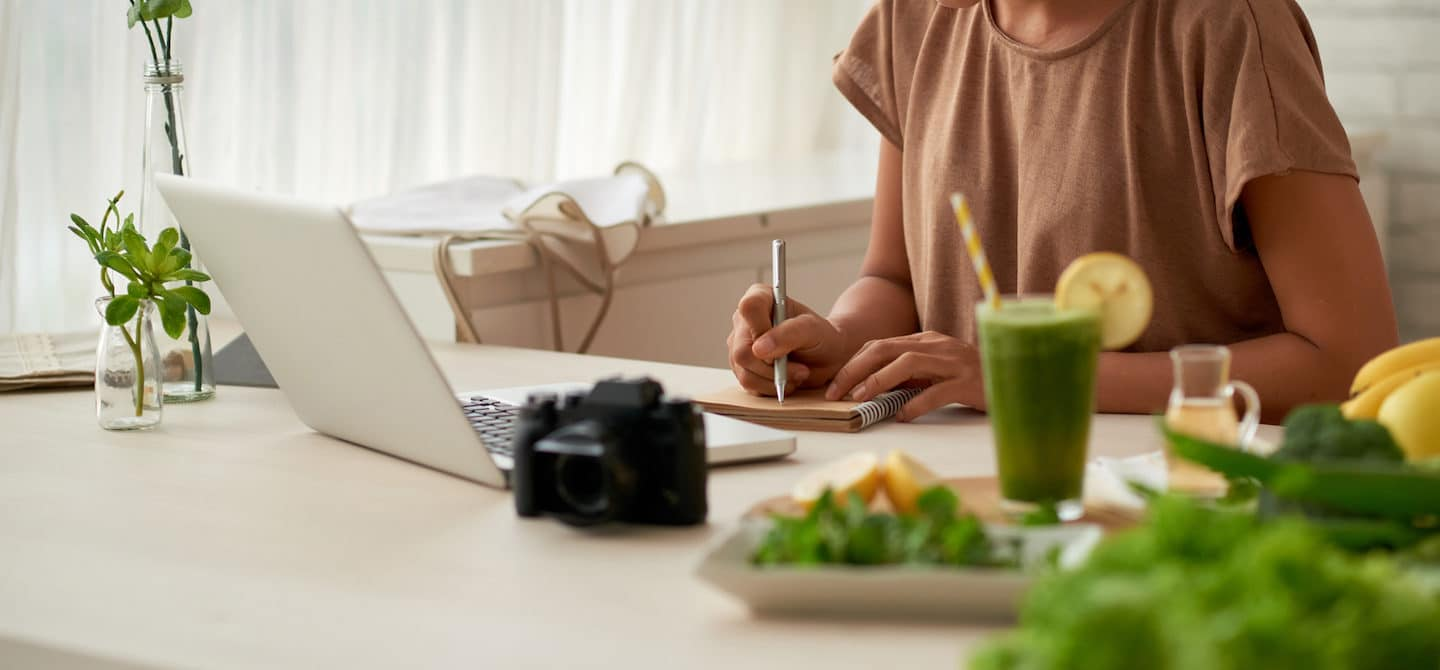 Woman writing a food diary at her kitchen table, planning to start an elimination diet