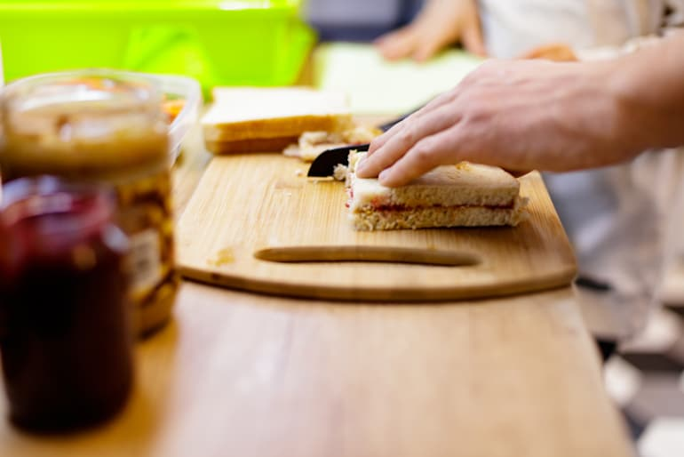 Man making a peanut butter and jelly sandwich to satisfy his craving for fatty foods