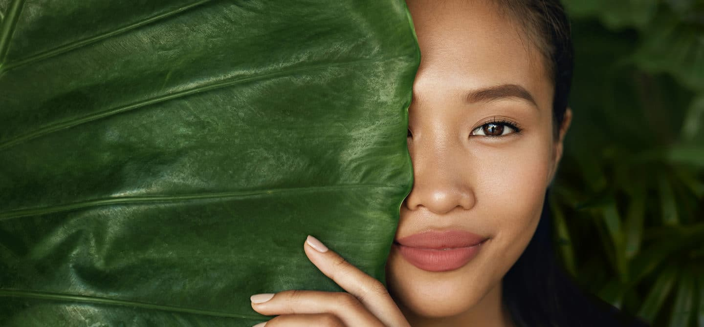beautiful woman who made plant-based skincare swaps half hidden behind a big leaf