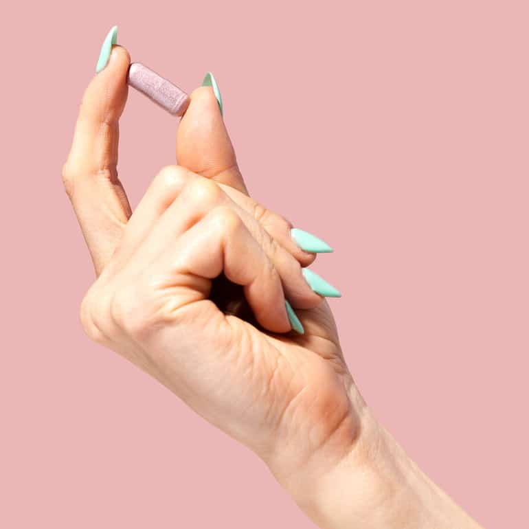Woman's hand holding HUM Nutrition Private Party vaginal probiotic in front of pink background