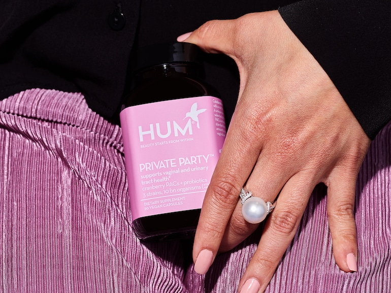 Woman's hand holding HUM Private Party vaginal probiotic supplement in front of her purple skirt