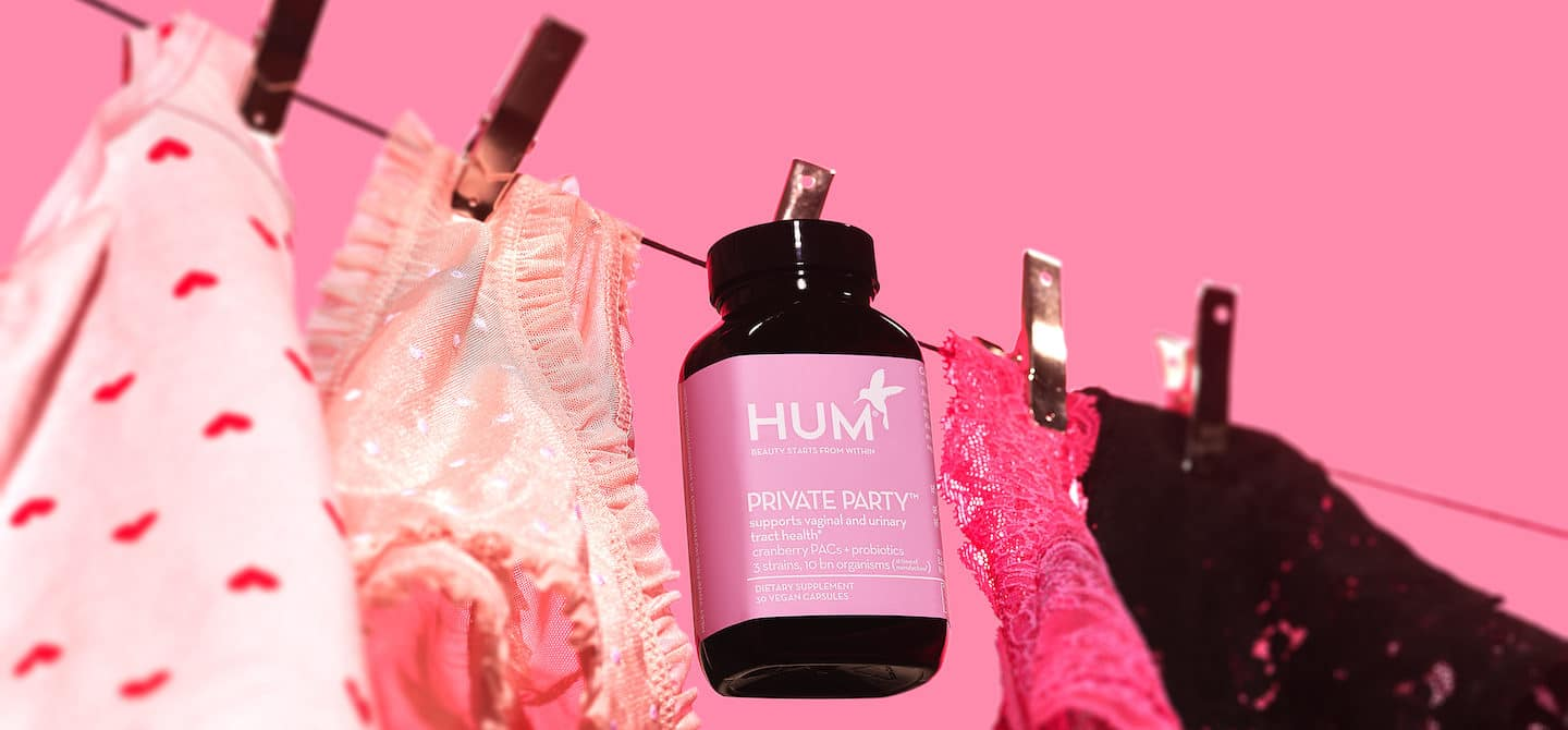 HUM Nutrition Private Party probiotic for vaginal health on clothing line with lingerie over pink background