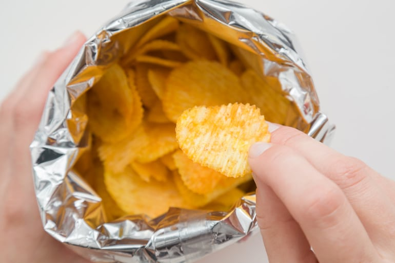 Woman's hand reaching into a bag of potato chips to satisfy her salty food craving