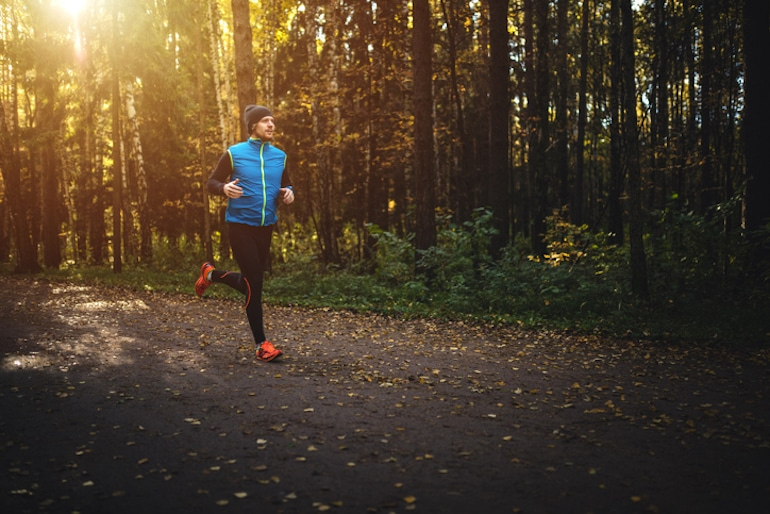 Man running in solitude at daybreak through the forest, who prizes fitness and the importance of alone time