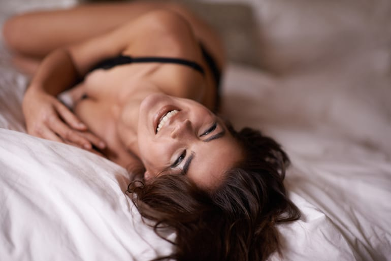Woman in lingerie smiling in bed after using the best types of sex toys for women