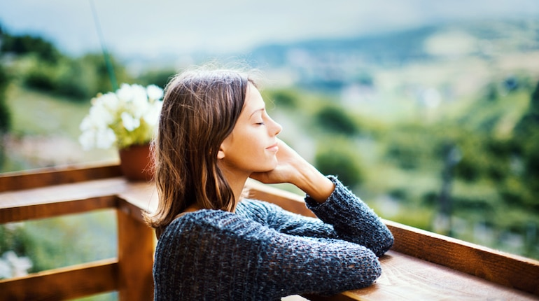 Woman on balcony with eyes closed, recognizing the importance of alone time and pleasant solitude