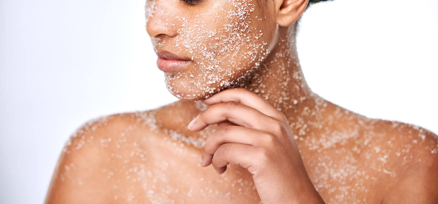 Woman using physical exfoliants on her face, neck, and decolletage