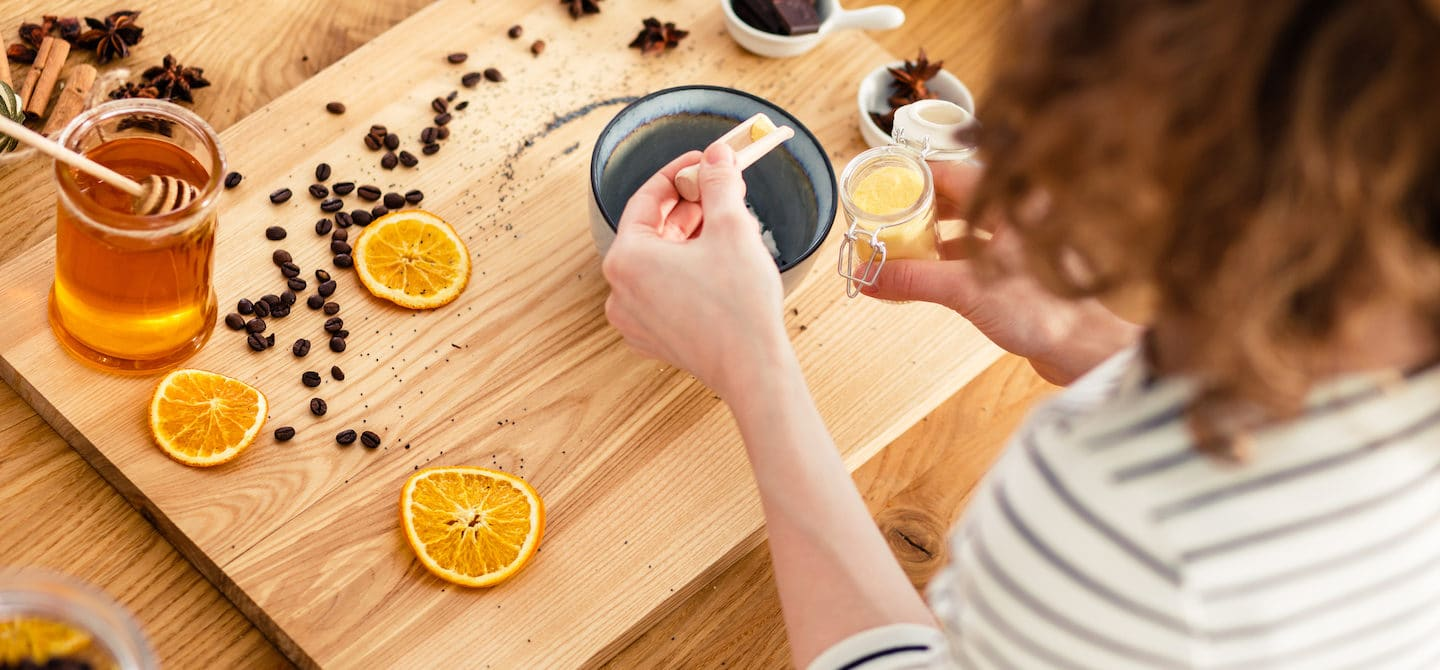 Woman making DIY beauty recipes with sugar, lemon, coffee, and other pantry staples