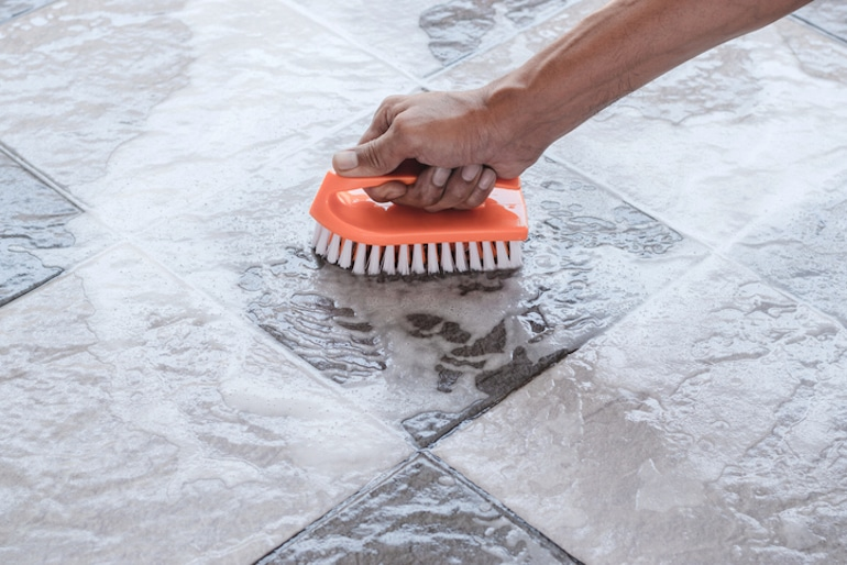 Man scrubbing the floor with a brush, keeping busy while social distancing