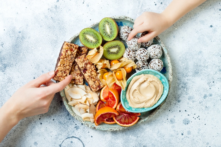 Two people reaching for healthy snacks, like kiwi and energy balls, to beat sugar cravings